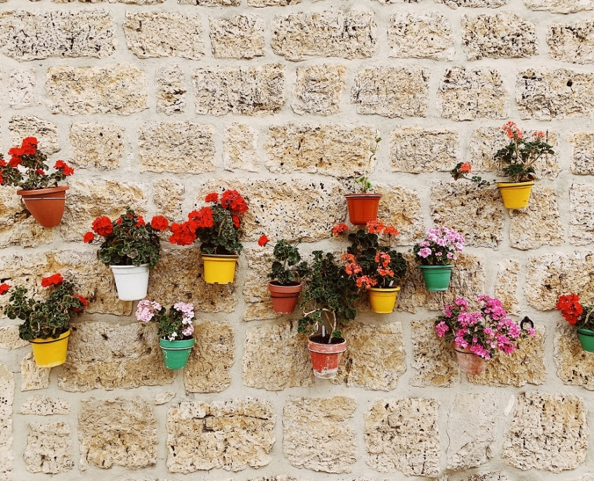 Vrolijk gekleurde bloempotten aan stenen muur